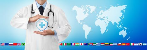 International travel medical insurance concept, doctor`s hands protect an shield cross icon, on blue background with. World map and flags, web banner template stock photography