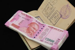 International Travelers Money. New Indian currency notes issued after demonetization of old currency notes with Border stamp impression on passport Royalty Free Stock Photography