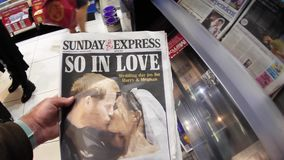 International Uk Newspaper about Royal Wedding. London, England - May 20, 2018: POV The Sunday Express front cover newspaper in British press kiosk featuring stock video footage