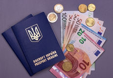 International Ukrainian passport with Euro banknotes isolated on gray background. Royalty Free Stock Images