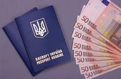 International Ukrainian passport with Euro banknotes isolated on gray background. Royalty Free Stock Photos
