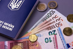 International Ukrainian passport with Euro banknotes isolated on gray background. Stock Photo