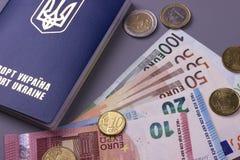 International Ukrainian passport with Euro banknotes isolated on gray background. Stock Photos