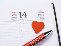 International Valentine. A detail of the Valentine day - February 14 page in a calendar with a red heart and a red decorated pen Royalty Free Stock Photo