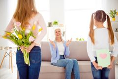 International woman`s day comfort concept. Mum hiding tulips beh. Ind back kid card with heat for astonished excited cheerful amazed shocked wondered impressed Stock Photography