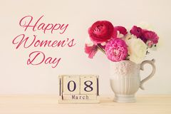 International women day concept with beautiful flowers in the vase and date on wooden table. International women day concept with beautiful flowers in the vase Stock Photos