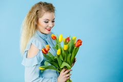 Pretty woman with red yellow tulips bunch royalty free stock photography