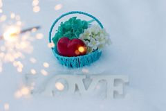 International women day. March 8 and Valentine`s day. Basket with flowers on a white snow background. Bengal fire with sparks and beautiful bokeh royalty free stock photo
