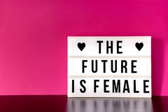 International Women`s Day - concept - `The future is female` - light box with cinema style lettering on hot pink background. With copy space Royalty Free Stock Image