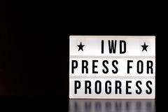 International Women`s Day - concept - `Press for Progress` 2018 theme - light box with cinema style lettering on black background. With copy space Stock Photos