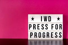 International Women`s Day - concept - `Press for Progress` 2018 theme - light box with cinema style lettering on hot pink backgrou. Nd with copy spacen Stock Photography