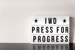 International Women`s Day - concept - `Press for Progress` 2018 theme - light box with cinema style lettering on white background. With copy space Royalty Free Stock Image