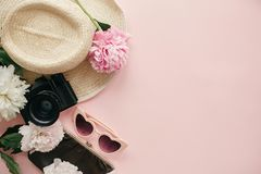 International Women`s Day flat lay. Stylish girly image of peonies, photo camera, retro sunglasses, hat, purse on pastel pink. Paper with copy space. Hello stock photo