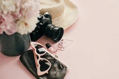 International Women`s Day. Stylish girly image of pink peonies, photo camera, retro sunglasses, jewelry, nail polish, hat, purse. On pastel pink paper with copy royalty free stock image