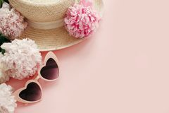 International Women`s Day. Stylish girly pink retro sunglasses, white and pink peonies, straw hat on pastel pink paper with copy. Space. Hello spring concept stock photography