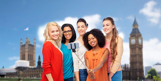 International women taking selfie in london. Travel, tourism and people concept - international group of happy smiling different women taking picture with Stock Photos