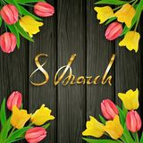 8th March Womens Day on black wooden background with tulips. International Womens Day on black wooden background with tulips. Golden lettering 8th March Stock Images