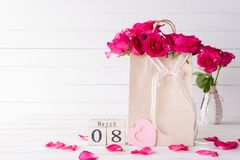 International Womens day concept. Pink roses in paper bag with March 8 text on wooden block calendar on white wooden background royalty free stock photo
