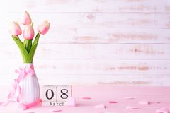 International Womens day concept. Pink tulips and red heart with March 8 text on wooden block calendar on white wooden background stock photography