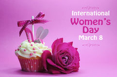 International womens day cupcake. Happy International Womens Day greeting with pink rose and cupcake with high heel shoe on pink background with sample text Royalty Free Stock Photos