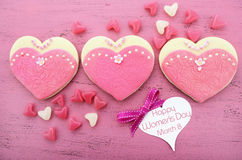 International Womens Day, March 8, heart shape cookies. Decorated as pink ladies dresses on vintage pink wood background stock photos