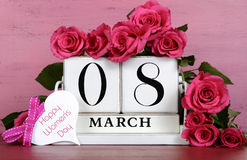 International Womens Day white vintage wood block calendar. Date for MArch 8, with roses on pink and red vintage wood background stock photos