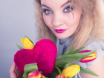 Woman holds tulips and red heart stock images
