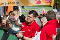 International Workers' Day. 1 May 2016, Berlin, Germany. BERLIN - MAY 01, 2016: A man with a child in her arms. Members of trade unions, workers and employees at royalty free stock photos