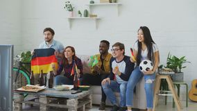 International young friends watching olympic games match on TV together at home. Some of them happy about German team. International young friends watching stock footage