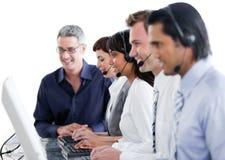 Internationale bedrijfsmensen die oortelefoon met behulp van Stock Afbeeldingen