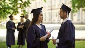 Internationale gediplomeerden met diploma's die gesprek, studentenuitwisseling hebben stock fotografie