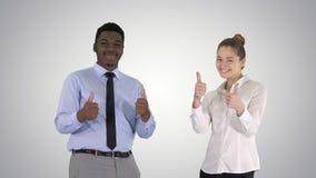 Internationale gelukkige glimlachende man en vrouw die duimen op gradiëntachtergrond tonen royalty-vrije stock afbeelding