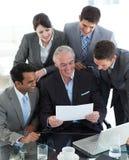 Internationale Geschäftsleute, die ein Dokument studieren Stockbild
