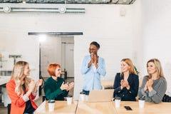 Internationale Gruppe glückliche Frauen, die Erfolg bei der Teambesprechung feiern lizenzfreie stockfotografie