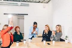Internationale Gruppe glückliche Frauen, die Erfolg bei der Teambesprechung feiern stockfotografie