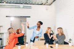 Internationale Gruppe glückliche Frauen, die Erfolg bei der Teambesprechung feiern lizenzfreie stockbilder