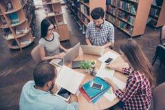 Internationale Gruppe von vier fokussierte kluges junges Studenten bookwo lizenzfreies stockfoto