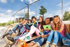 Internationale Kinder sitzen auf hölzernem Bau Stockbild