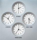 Internationale klokken met 4 verschillende tijdzones stock foto