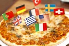 Internationale Markierungsfahnen auf Pizza Stockfotografie