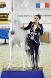 Internationale Paardtentoonstelling Moskou die Hall Woman-jockey in een donkerblauw kostuum bevrijden dichtbij aan een paard Stock Foto