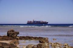 Internationale Schifffahrt durch Behälter-Frachtschiff am Abend zum Kunden, zur Logistik, zum Fracht-Transport und zum Versand Stockfoto