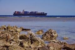 Internationale Schifffahrt durch Behälter-Frachtschiff am Abend zum Kunden, zur Logistik, zum Fracht-Transport und zum Versand Stockfotografie