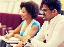 Internationale studenten met notitieboekjes op lezing royalty-vrije stock afbeeldingen