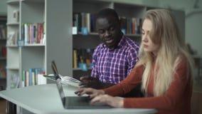Internationale Studenten studieren zusammen in der Bibliothek stock video