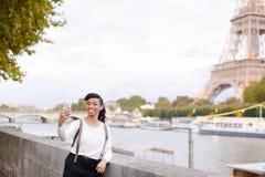 Internationale zwarte student die dichtbij de Toren en de Zegen van Eiffel lopen en selfie door smartphone, in Parijs maken royalty-vrije stock afbeelding