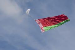 Internationaler Parachuter's Team Performing in einer Luft beim Abwickeln der Staatsflagge des Republik Belarus Lizenzfreie Stockbilder