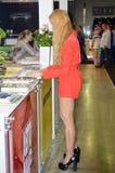 Internationaler stehen junge blonde Frauen Automobil-Salon Taffic Moskaus im kurzen roten Kleid nahe Zeitschriften lizenzfreies stockfoto