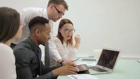 Internationales Team mit Führer am Kopf analysiert Zeitplan auf Laptop stock footage