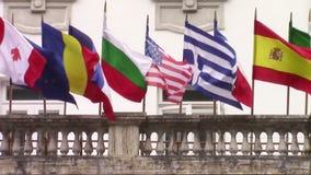 Internationalflaggor som vinkar i vinden stock video